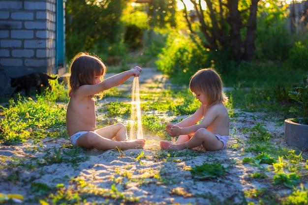 Les filles jouent avec du sable dans la cour