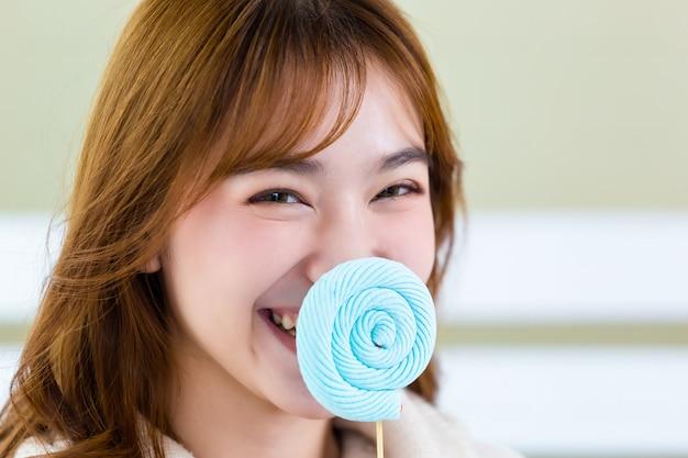 Les filles jouent et rigolent avec des sucettes bleues