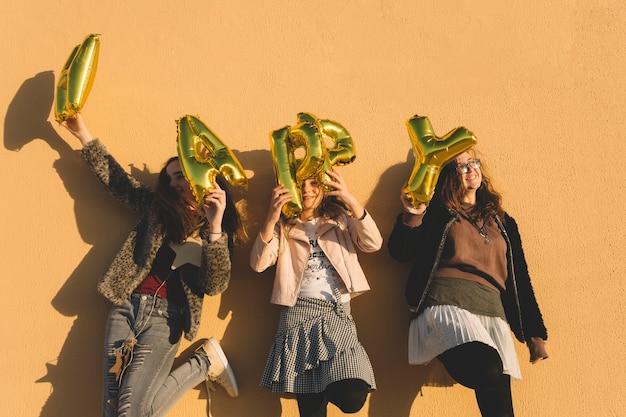 Filles joyeuses avec des ballons de lettre