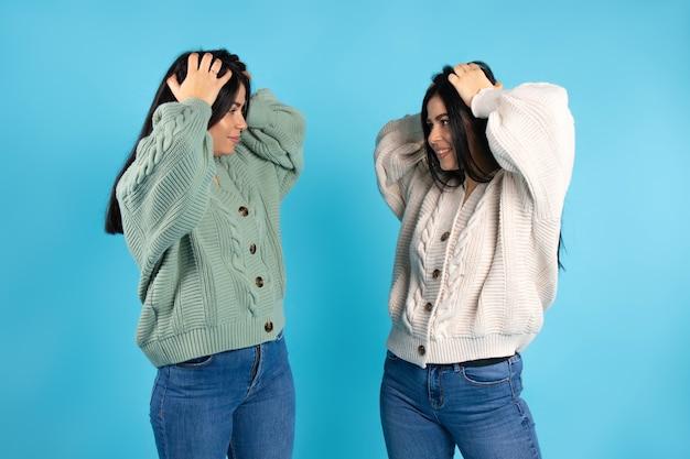 Des filles jumelles se tiennent les deux mains sur la tête en étant étonnées de se regarder