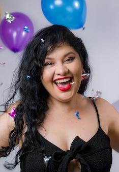 Filles latino-américaines posant et célébrant la nouvelle année avec des ballons et des confettis