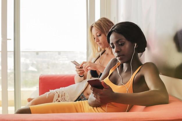 Des filles à la maison vérifient leur téléphone