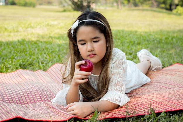 Les filles mangent des pommes sur le tapis.