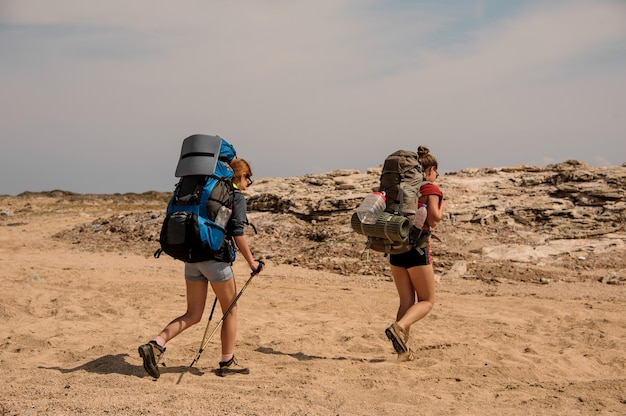 Filles marchant dans le désert avec sac à dos de randonnée