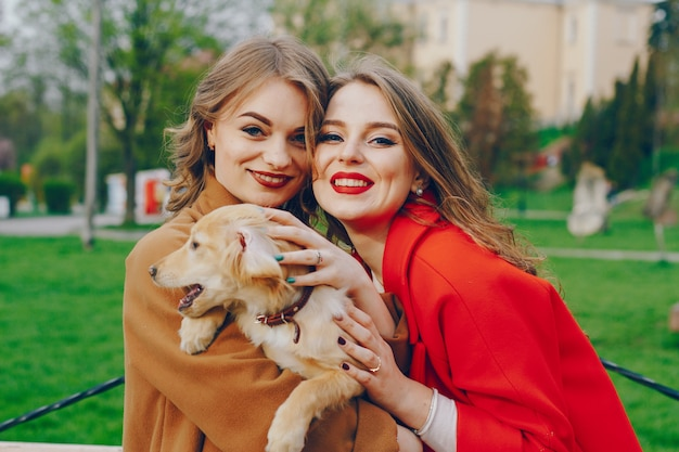 Les filles marchent dans le parc avec un chien