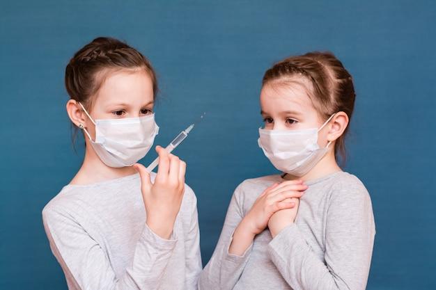 Les filles masquées regardent une seringue avec des médicaments dans les mains et ont peur. vaccination, traitement des enfants. prévention des épidémies