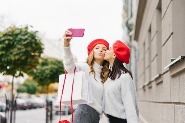 Les filles mignonnes lumineuses dans les bérets rouges et les chandails légers font un selfie au téléphone