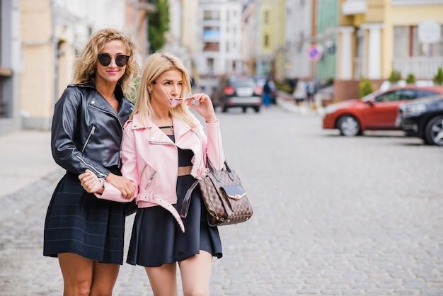 Des filles à la mode dans des lunettes de soleil debout sur la rue