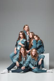 Filles de la mode debout ensemble et regardant la caméra sur studio gris