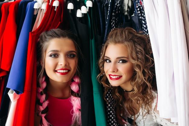 Filles à la mode heureuse s'amuser ensemble, passer du temps au magasin.