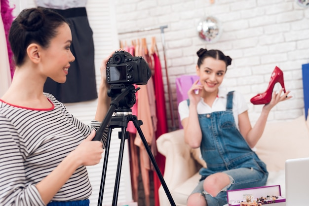 Les filles de la mode tiennent des chaussures rouges avec une fille.