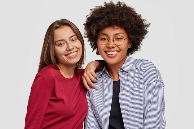 Des filles multiethniques amicales s'amusent ensemble, se réjouissent d'une journée de travail réussie