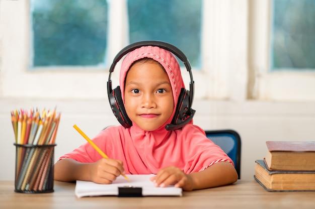 Filles musulmanes qui étudient en ligne à la maison pour réduire la distance sociale et prévenir les maladies transmissibles