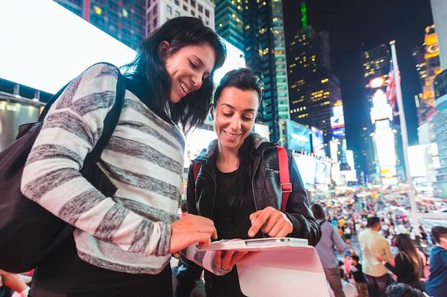 Filles à new york la nuit en regardant un téléphone intelligent