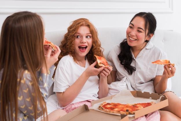 Filles pijama fête nuit conversation avec pizza