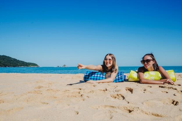 Les filles à la plage pointant