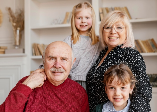 Filles de plan moyen et grands-parents prenant des photos