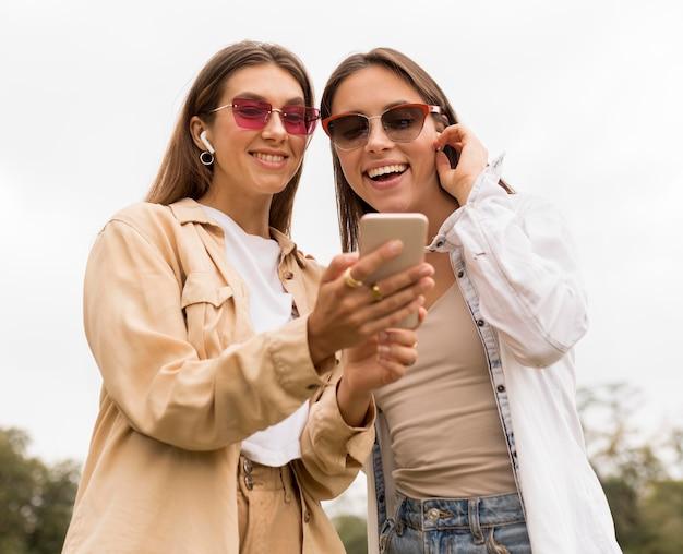 Filles de plan moyen regardant téléphone