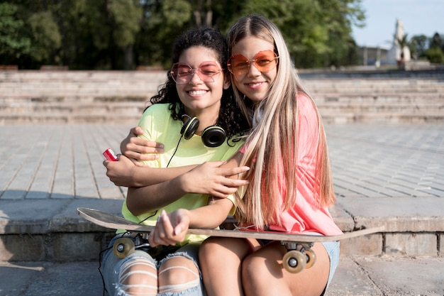 Filles de plan moyen avec skateboard assis
