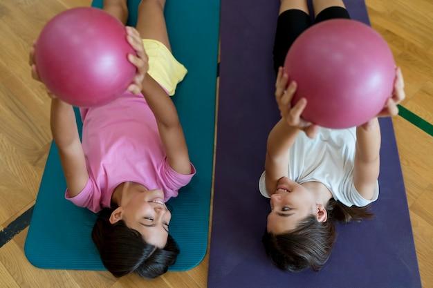 Filles de plan moyen sur des tapis de yoga