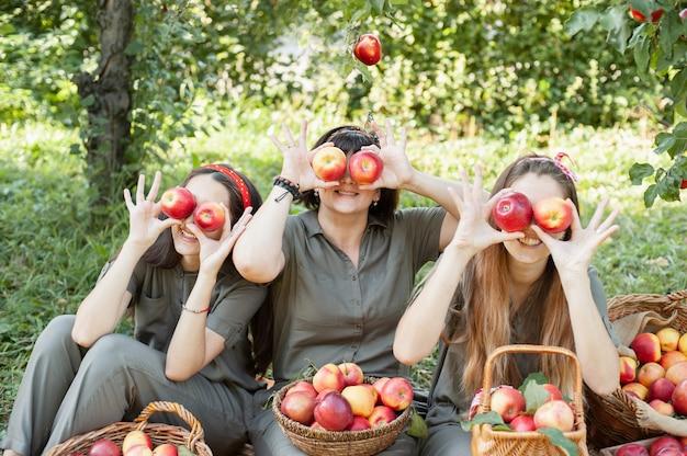 Filles avec pomme dans le verger de pommiers