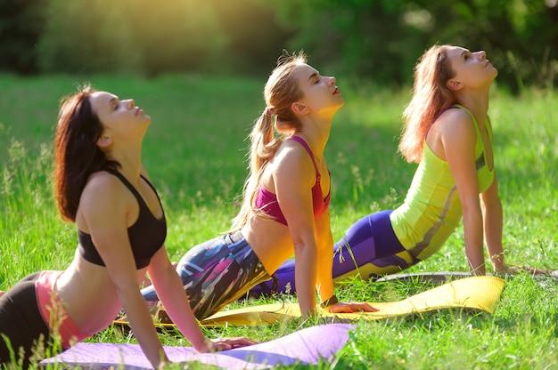 Filles posant le yoga à l'extérieur dans la forêt le matin
