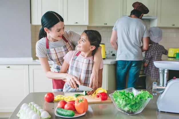 Les filles positives se regardent et sourient. la mère aide sa fille à couper les légumes correctement. papa cuisine de la nourriture avec son fils au poêle.