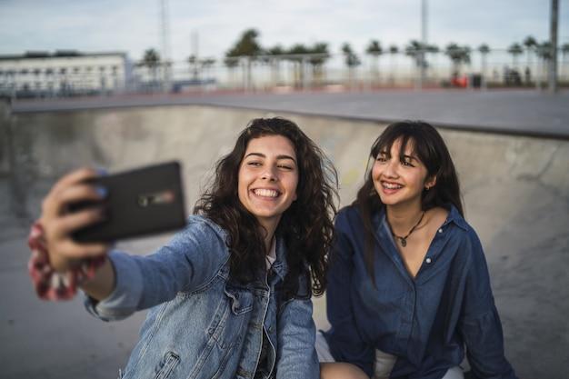 Filles prenant une photo d'elles-mêmes dans un skate park