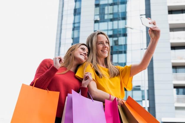 Filles prenant selfie après le shopping