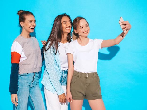 Filles, prendre, selfie, autoportrait, photos, sur, smartphone., modèles, poser, près, mur bleu, dans, studio, femme, projection, positif, figure, émotions