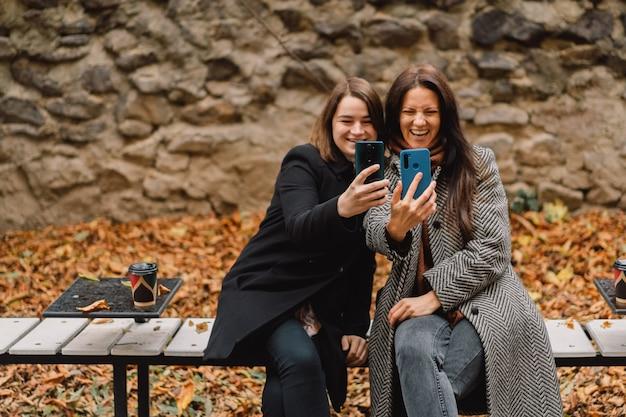 Les filles prennent un selfie au téléphone dans le parc. amis et style de vie