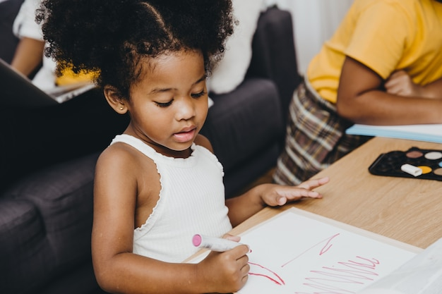 Filles préscolaires noires américaines faisant leurs devoirs apprenant l'éducation avec sa sœur vivant ensemble à la maison.
