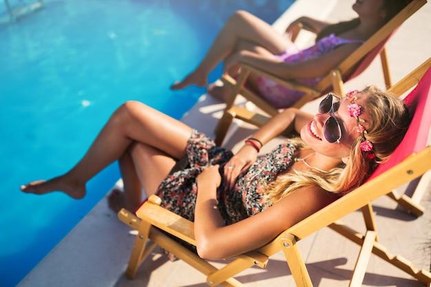 Filles profitant des vacances d'été dans des chaises de bronzage