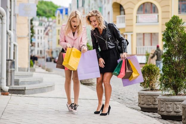 Les filles regardent dans le sac à provisions en souriant