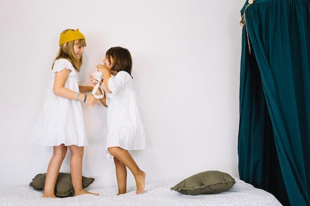 Filles en robes blanches parlant sur le lit