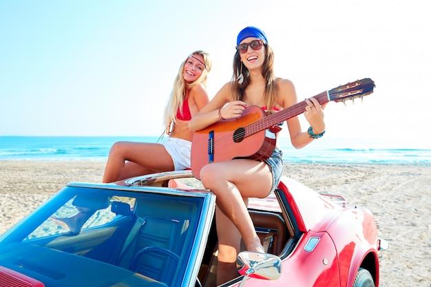 Filles s'amusant à jouer de la guitare sur la plage dans une voiture