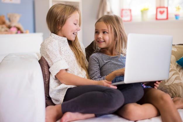 Filles s'amusant à utiliser l'ordinateur portable
