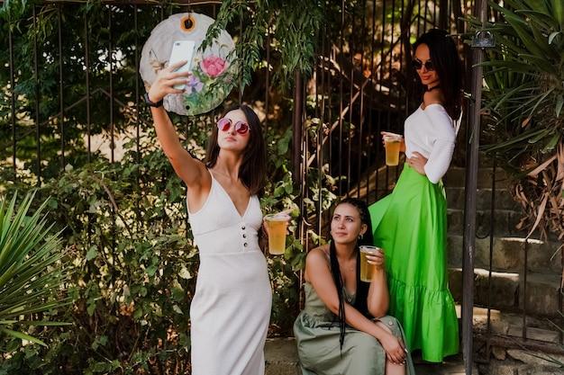 Les filles s'amusent, boivent des cocktails et prennent des selfies avec un smartphone
