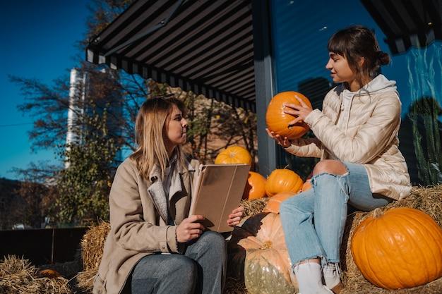 Les filles s'amusent parmi les citrouilles et les meules de foin dans une rue de la ville. une belle jeune fille assise sur des tas de foin. le concept de zones rurales dans une ville moderne. zone photo