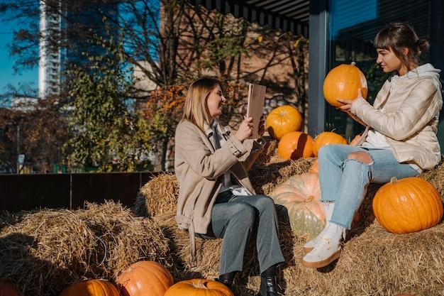 Les filles s'amusent parmi les citrouilles et les meules de foin dans une rue de la ville