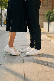 Les filles se tiennent sur la pointe des pieds pour embrasser son homme - gros plan sur les chaussures