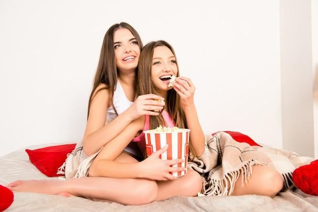 Filles sexy sorties regardant un film et mangeant du pop-corn