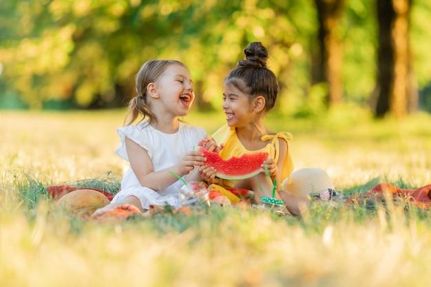 Les filles sont assises sur une couverture dans le parc et mangent une tranche de pastèque collation saine pour les enfants