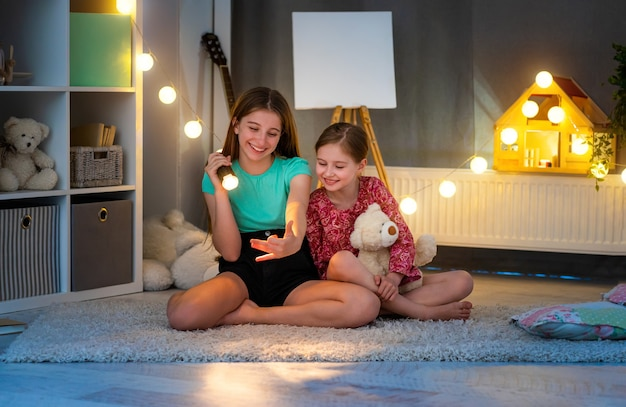 Filles souriantes faisant du théâtre d'ombres à la main à l'aide d'une lampe de poche dans la chambre des enfants