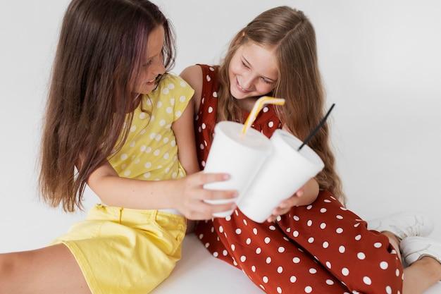 Filles souriantes de plan moyen tenant des tasses