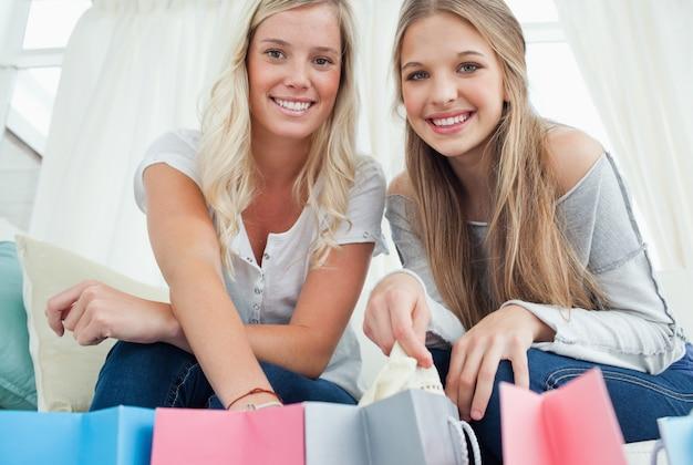 Les filles sourient en regardant la caméra avec des sacs