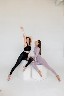 Les filles sportives athlétiques se tiennent en retrait avec un beau cul de fessesfitness et des instructeurs de yoga en combinaisons d'entraînement posent sur fond blanc