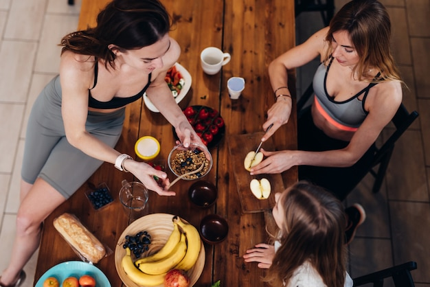 Filles sportives dans la cuisine préparant des repas faciles.