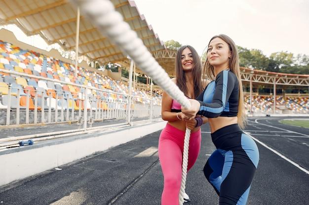 Filles sportives dans une formation uniforme avec une corde au stade