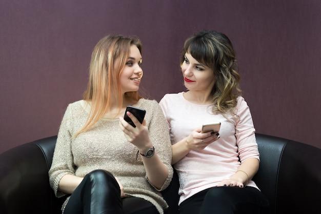 Filles avec des téléphones portables dans leurs mains.